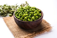 Fresh Green Chickpeas or Chick peas also known as harbara or harbhara. In hindi and Cicer is scientific name, served in a wooden bowl or plate. selective focus royalty free stock photos