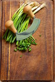 Fresh green chives on wooden board with knife Royalty Free Stock Photos