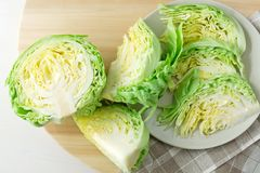 Fresh chopped head of cabbage. Fresh green chopped and sliced cabbage on wood cutting board, prepare for salad. Homemade cooking concept stock photography