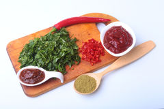 Fresh green cilantro, coriander leaves, tomato paste, chili pepper and spices on a wooden board. Ingredients for meat Royalty Free Stock Photo