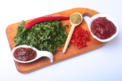 Fresh green cilantro, coriander leaves, tomato paste, chili pepper and spices on a wooden board. Ingredients for meat Royalty Free Stock Images