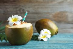Fresh green coconut with drinking straw. On wooden table Royalty Free Stock Images