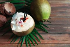 Fresh green coconuts and palm leaf. On wooden table Stock Images