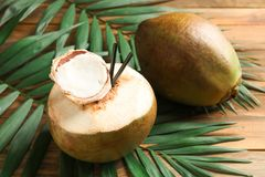 Fresh green coconuts and palm leaves. On wooden table Royalty Free Stock Photo