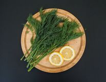 Fresh green dill on a wooden cutting board with lemon on the black background stock images