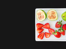Fresh green figs and strawberries on a white ceramic board on bl Royalty Free Stock Photo