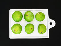 Fresh green figs on a white ceramic board on black Royalty Free Stock Photos