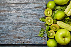 Fresh green fruits and vegetables. Collection of fresh green fruits and vegetables on a dark wooden background stock photo