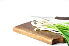 Fresh green garlic on the board with a knife royalty free stock photo