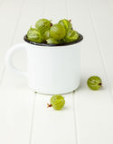 Fresh green gooseberries in an enamel mug Stock Photo