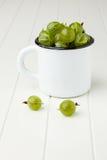 Fresh green gooseberries in an enamel mug Royalty Free Stock Photos