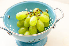 Fresh green grapes in a blue metal colander Royalty Free Stock Images