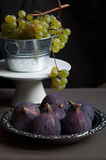 Fresh green grapes and figs. Fresh green grapes in metal bucket against dark background with figs on a platter Stock Images