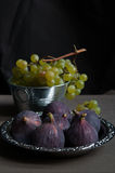 Fresh green grapes and figs. Fresh green grapes in metal bucket against dark background with figs on a platter Royalty Free Stock Image