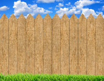 Fresh Green Grass Over Wood Fence Background And Blue Sky Stock Images