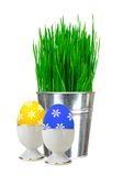 Fresh green grass in small metal bucket and Easter egg in stand Stock Image