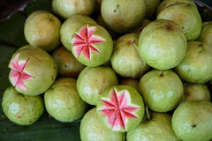 Fresh green guava street food with pink pulp and seeds selling o Stock Image