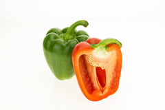 Fresh green and half cut red bell peppers Royalty Free Stock Images