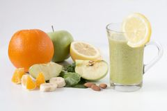 Fresh green healthy smoothie with fruits and vegetables. Glas of healthy smoothie with spinach leaf and ts including orange, banana, almond, lemon and green royalty free stock photos