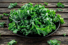 Fresh green healthy superfood vegetable kale leaves in a black plate on wooden rustic table Royalty Free Stock Photo