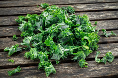 Fresh green healthy superfood vegetable kale leaves on wooden rustic table Stock Image
