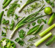 Fresh green herbs and vegetables. Various fresh green herbs and vegetables on gray background, top view Stock Images