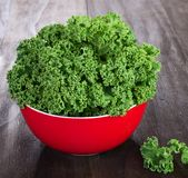 Fresh green kale leaves. In red ceramic bowl on vintage wooden table Royalty Free Stock Photography