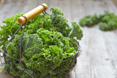 Fresh green kale leaves. On wooden table Royalty Free Stock Image