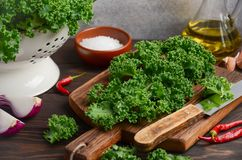Fresh green kale with olive oil and spices, ready for cooking. Selective focus Stock Photo