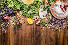 Fresh green kale and vegetables ingredients for cooking on rustic wooden background. Top view, border Stock Photos