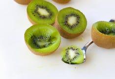 Fresh green kiwis. Fresh kiwis and a tea spoon on a white plastic cutting board royalty free stock photo