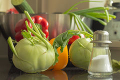 Fresh green kohlrabis, red and yellow paprika, a salt shaker. Stock Photo