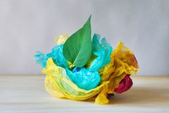 Green leaf and used crumpled colorful plastic bags and wraps on wooden table. Fresh green leaf and used crumpled colorful plastic bags and wraps on wooden table royalty free stock photo
