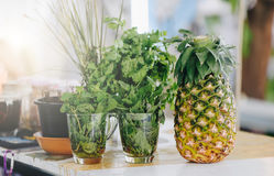 Fresh green leaves in glasses and pineapple on the bar counter Royalty Free Stock Photo