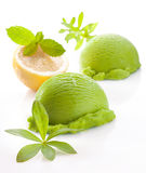 Fresh green lemon or lime icecream. Scoops of fresh green lemon or lime icecream on a white studio background with faint reflection royalty free stock photos