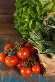 Fresh green lettuce salad, italian kitchen herbs and tasty cherr. Fresh green lettuce salad, italian herbs and tasty cherry tomatoes on vine on wooden table Stock Photography