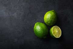 Fresh green lime on black background. Top view, copy space royalty free stock photo