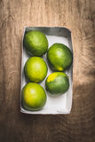Fresh green lime in paper box on rustic wooden background Stock Image