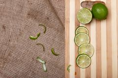 Fresh green lime with slices on wooden bamboo kitchen board Royalty Free Stock Image