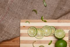 Fresh green lime with slices on wooden bamboo kitchen board Stock Photos