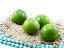 Fresh green lime and tablecloth on white background Stock Photography