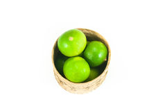 fresh green limes in the bamboo basket isolated on white background Stock Photo