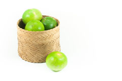 Fresh green limes in the bamboo basket isolated on white background Stock Image