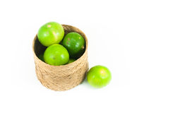 Fresh green limes in the bamboo basket isolated on white background Royalty Free Stock Photo