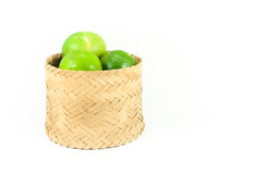Fresh green limes in the bamboo basket isolated on white background Royalty Free Stock Photos