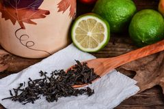 Fresh green limes and black tea Royalty Free Stock Images