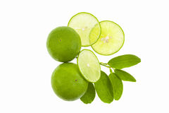 Fresh green limes with slices and leaf isolated on white backgro Royalty Free Stock Photos