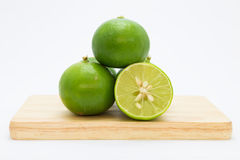 Fresh green limes on wooden board Stock Images