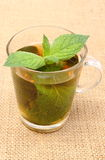 Fresh green mint in cup of beverage on burlap texture Royalty Free Stock Image