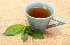 Fresh green mint and cup of beverage on jute canvas Royalty Free Stock Images